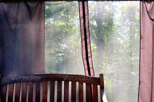 Summerhouse bench and view through net to nature - Stock Photo - Images