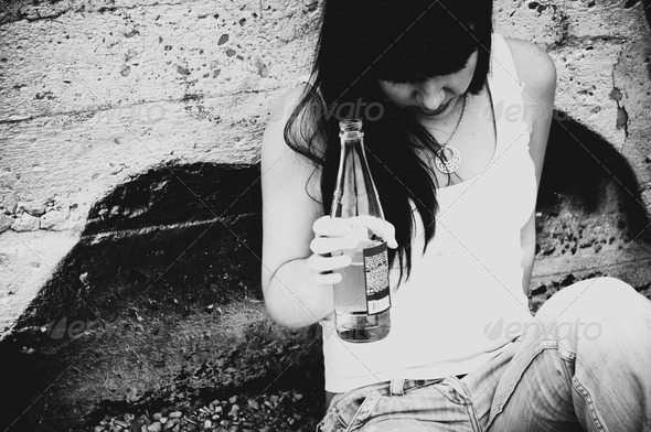 Drunk young girl with a bottle of beer
