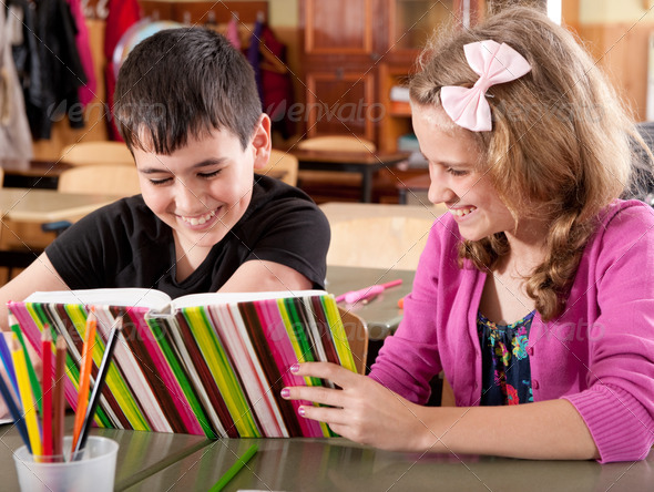 Smiling boy and girl reading book at school - Stock Photo - Images