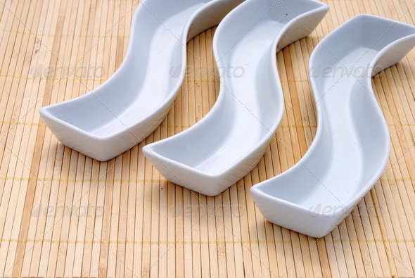 three white dishes over a bamboo placemat - Stock Photo - Images