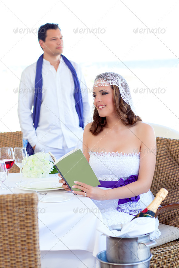 Couple in wedding day woman reading book on banquet - Stock Photo - Images