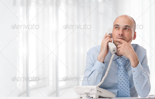 Businessman talking on landline phone at office - Stock Photo - Images