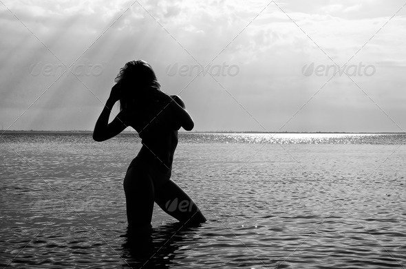 Black and white photo: Siluette of woman in the sea - Stock Photo - Images