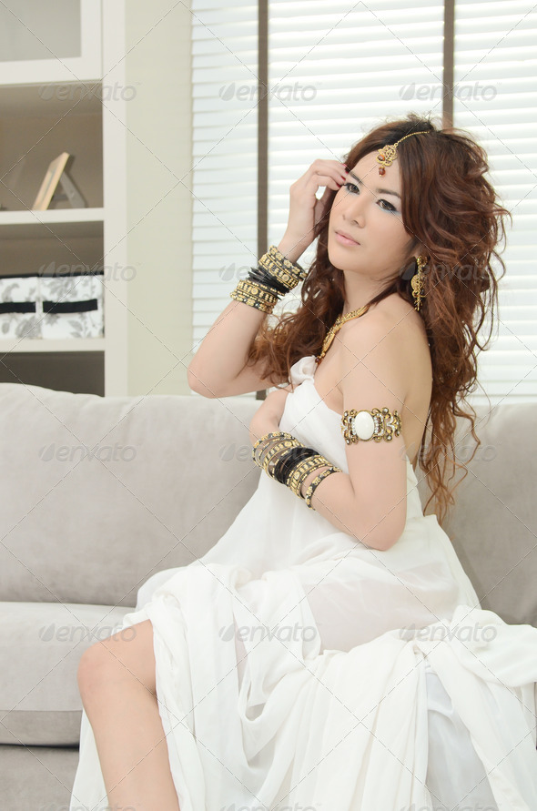 Beautiful luxurious woman sitting on modern sofa in living room - Stock Photo - Images