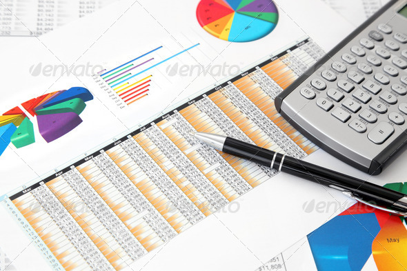 Calculator and Pen on the Investment Charts