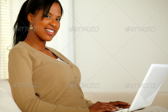 Pretty girl smiling at you while working on laptop - Stock Photo - Images