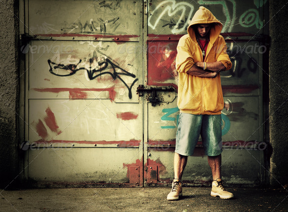 Young man in hooded sweatshirt on grunge wall - Stock Photo - Images
