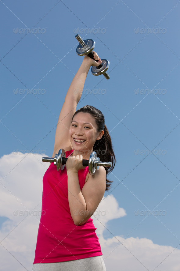 Chinese woman exercising with dumbbells. - Stock Photo - Images