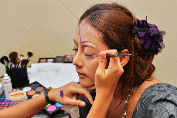 A beautiful young woman having the final touches applied to her make up - Stock Photo - Images
