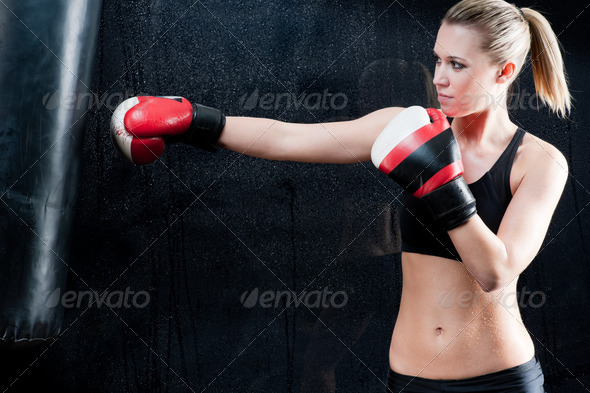 Boxing training woman in gym punching bag - Stock Photo - Images