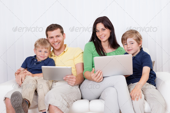 Happy family using laptop at home - Stock Photo - Images