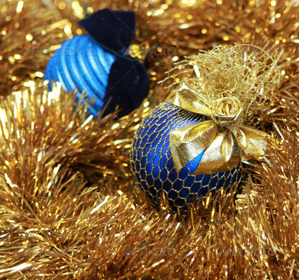 blue christmass balls on a golden tinsel - Stock Photo - Images