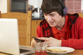 Teenage Boy Using Laptop And Listening To MP3 Player Whilst Eating Breakfast - PhotoDune Item for Sale