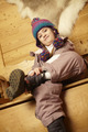 Young Girl Sitting On Wooden Seat Putting On Warm Outdoor Clothes And Boots - PhotoDune Item for Sale