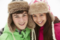 Portrait Of Teenage Couple In Snow Wearing Fur Hats - PhotoDune Item for Sale