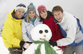 Group Of Friends Building Snowman On Ski Holiday In Mountains - PhotoDune Item for Sale
