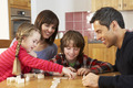 Family Playing Dominoes In Kitchen - PhotoDune Item for Sale