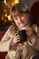 Young Girl Relaxing With Hot Drink By Cosy Log Fire - PhotoDune Item for Sale