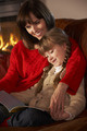 Mother And Daughter Sitting On Sofa And Reading Book By Cosy Log Fire - PhotoDune Item for Sale