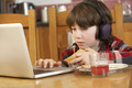 Boy Using Laptop Whilst Eating Breakfast - PhotoDune Item for Sale