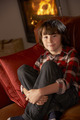 Young Boy Sitting On Sofa By Cosy Log Fire - PhotoDune Item for Sale