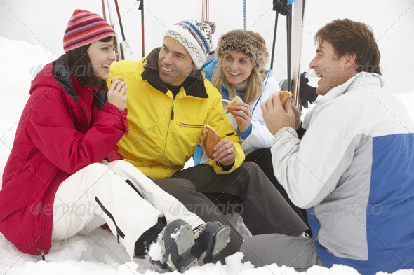 Group Of Middle Aged Friends Eating Sandwich On Ski Holiday In Mountains - Stock Photo - Images