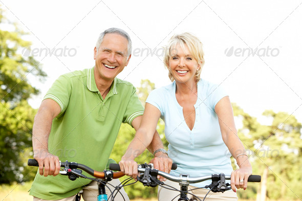 Mature couple riding bikes - Stock Photo - Images