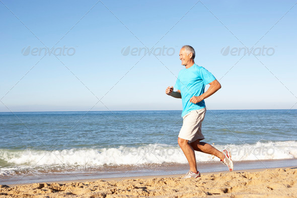 Senior Man In Fitness Clothing Running Along Beach - Stock Photo - Images