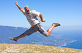 happy man jumping on a background of mountains and sky and sea - PhotoDune Item for Sale