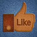 Like sign. Leather Thumbs up symbol on blue jeans background - PhotoDune Item for Sale