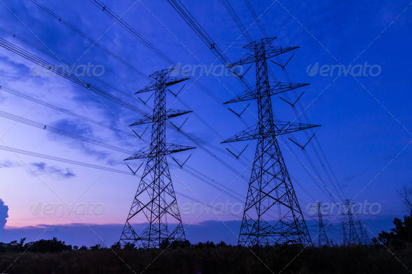 electricity high voltage power post at twilight evening - Stock Photo - Images
