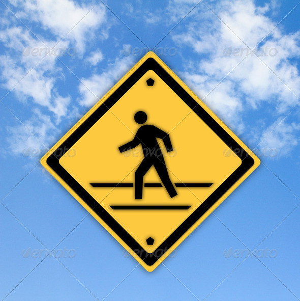 Crosswalk sign with a man walking on yellow with a blue sky back - Stock Photo - Images
