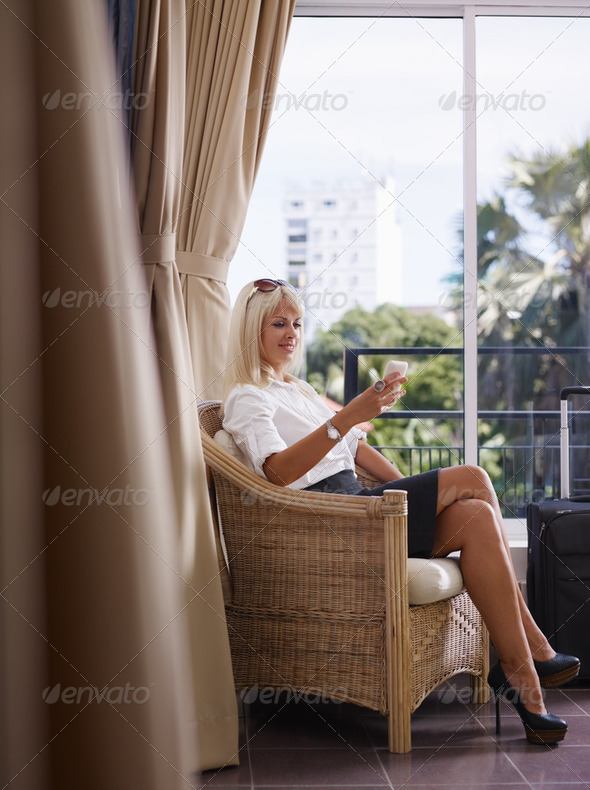 businesswoman using mobile phone in hotel room - Stock Photo - Images