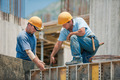 Two construction workers installing concrete formwork frames - PhotoDune Item for Sale