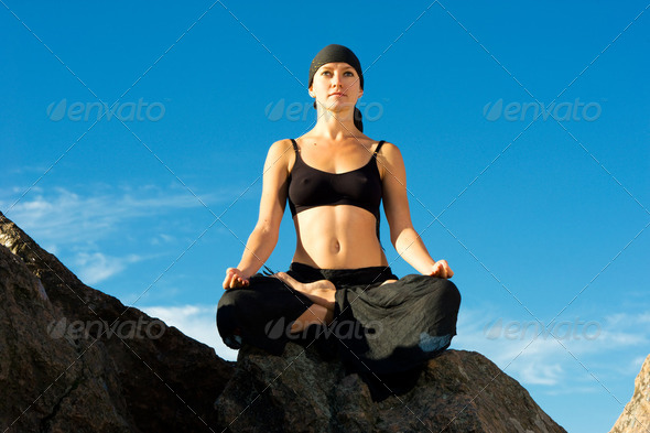 beautiful woman sitting in lotus pose on the beach - Stock Photo - Images