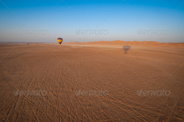 Hot Air Balloon floating over the desert sand - Stock Photo - Images