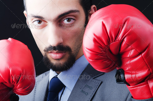 Young businessman with boxing gloves - Stock Photo - Images