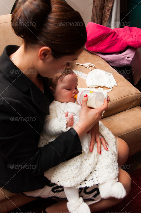 Young mother feeding baby girl on her lap from a milk bottle - Stock Photo - Images