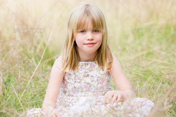 Young girl sitting outdoors smiling - Stock Photo - Images