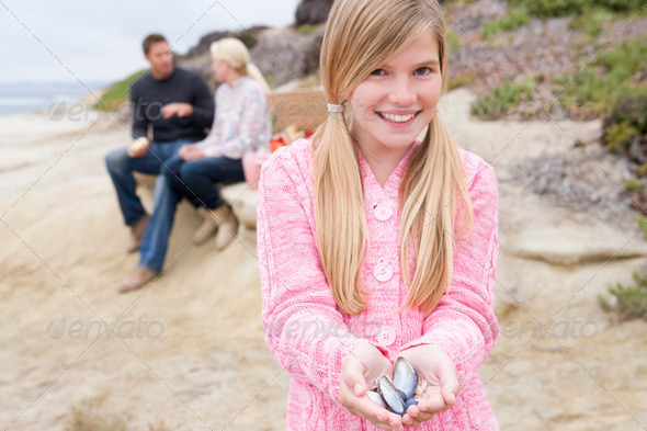 Family at beach with picnic smiling focus on girl with seashells - Stock Photo - Images