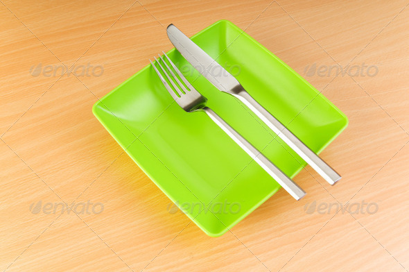 Plate with utensils on wooden table - Stock Photo - Images