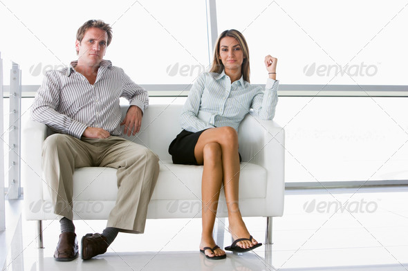 Two businesspeople sitting in office lobby smiling - Stock Photo - Images