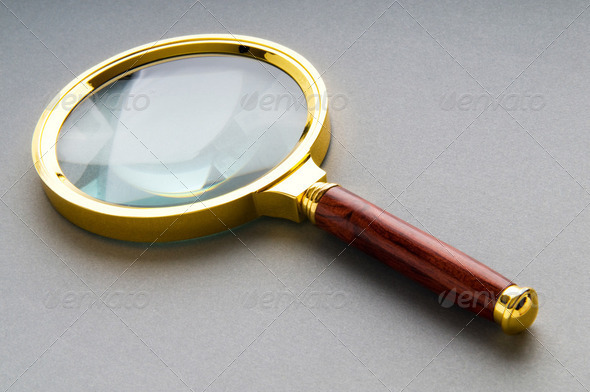 Magnifying glass with wooden handle on the flat surface - Stock Photo - Images