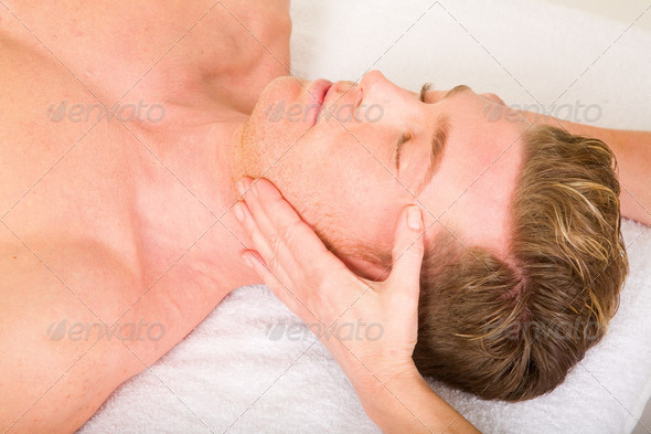 young man receives a face massage - Stock Photo - Images