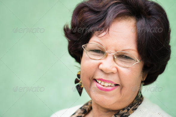 Portrait of happy elderly black lady with eyeglasses smiling - Stock Photo - Images