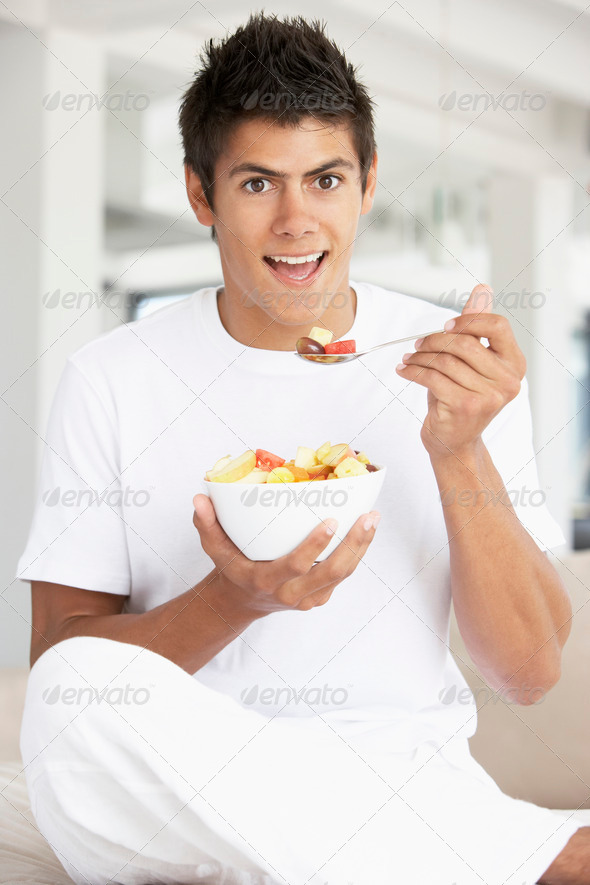 Young Man Eating Fresh Fruit Salad - Stock Photo - Images