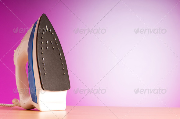 Modern electric iron against the colorful background - Stock Photo - Images