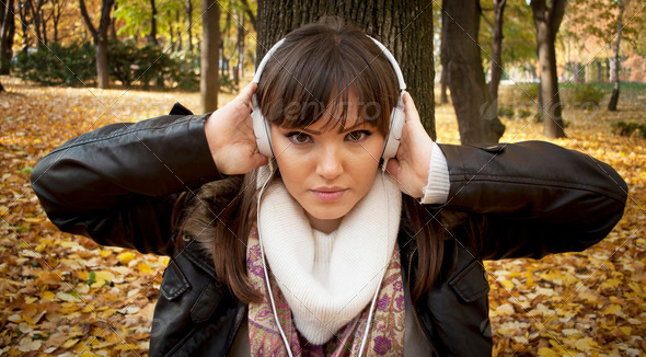 Close-up of a beautiful woman listening music outdoor - Stock Photo - Images