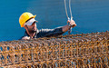 Construction worker loading stack of reinforcement beam cages to crane - PhotoDune Item for Sale