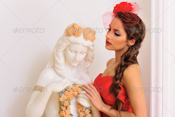beautiful woman in red with antique statue. - Stock Photo - Images